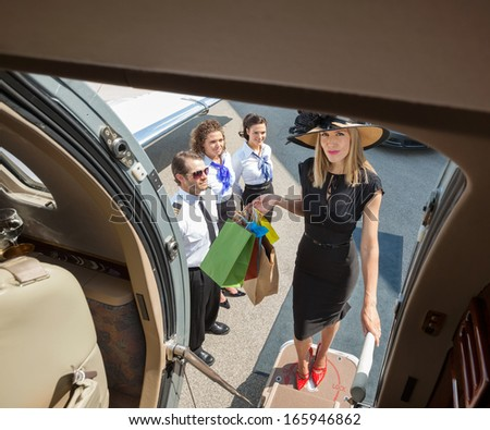 Full length portrait of rich woman with shopping bags boarding private jet while pilot and airhostess looking at her - stock photo