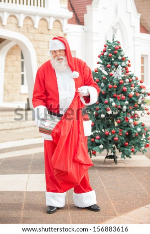 Full length portrait of Santa Claus putting present in bag outside house - stock photo