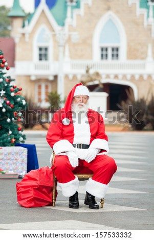 Full length portrait of Santa Claus sitting in courtyard - stock photo
