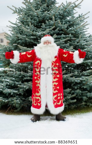 Full Length Portrait of Santa Claus standing with open hands outdoors at christmas tree. Snow falls. Natural light. - stock photo