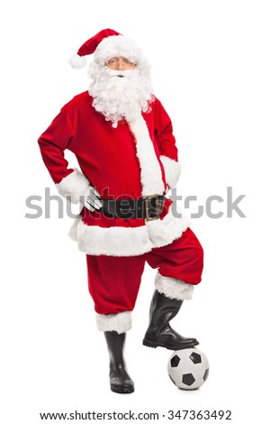Full length portrait of Santa Claus stepping over a football and looking at the camera isolated on white background - stock photo