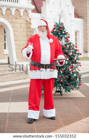 Full length portrait of Santa Claus with milk and cookies in courtyard - stock photo