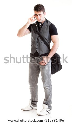 Full length portrait of school boy holding books and talking on mobile phone isolated on white background - stock photo
