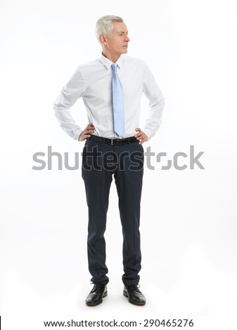 Full length portrait of senior businessman standing against white background while hand on the hip. - stock photo