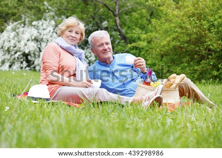Full length portrait of senior couple relaxing  and picnic at park. - stock photo