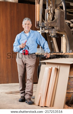 Full length portrait of senior male carpenter holding ear protectors by bandsaw in workshop - stock photo