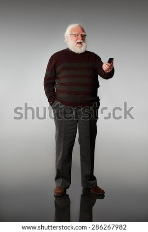 Full length portrait of senior man standing over grey background looking at mobile phone laughing - stock photo
