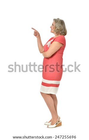 Full length portrait of senior woman pointing on white background - stock photo