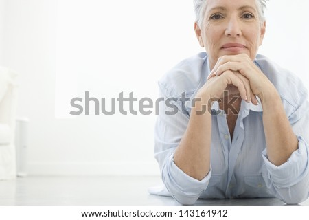 Full length portrait of senior woman with hands on chin lying on floor - stock photo