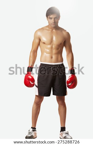 Full length portrait of shirtless young man wearing boxing gloves against white background - stock photo
