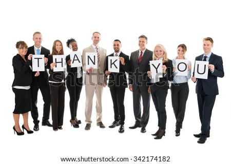 Full length portrait of smiling business team holding Thank You sign against white background - stock photo