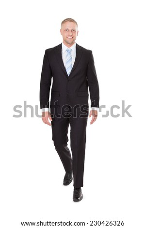 Full length portrait of smiling businessman walking over white background - stock photo