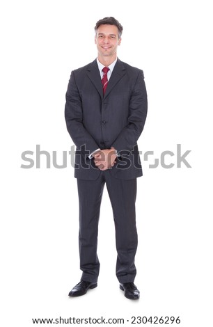Full length portrait of smiling businessman with hands clasped standing against white background - stock photo