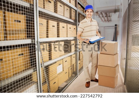 Full length portrait of smiling delivery man holding clipboard while standing by stacked cardboard boxes in warehouse - stock photo