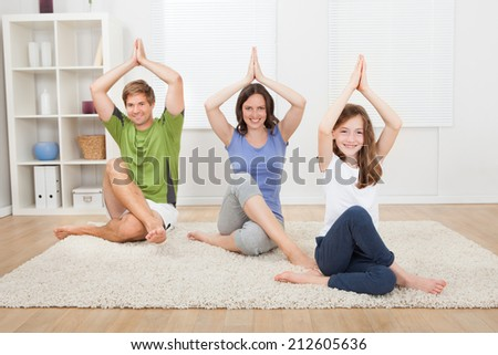Full length portrait of smiling family practicing yoga on rug at home - stock photo