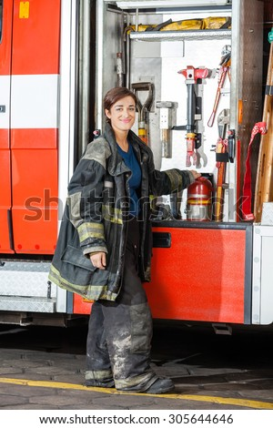 Full length portrait of smiling female firefighter standing by truck at fire station - stock photo