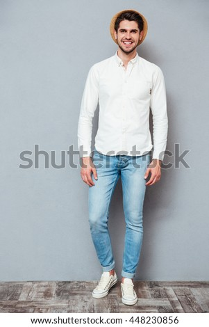 Full length portrait of smiling handsome young man in white shirt, jeans and hat standing over grey background