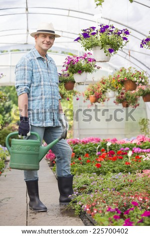 Full-length portrait of smiling man carrying watering can in greenhouse - stock photo