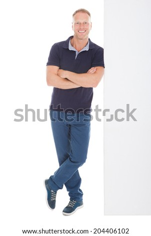 Full length portrait of smiling mid adult man standing arms crossed over white background - stock photo