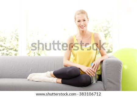 Full length portrait of smiling middle age woman taking a break at home after fitness workout.