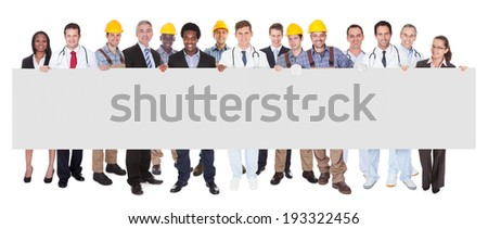 Full length portrait of smiling people with various occupations holding blank billboard over white background