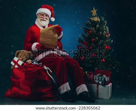 Full-length portrait of smiling Santa Claus with a Christmas letter