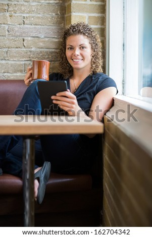 Full length portrait of smiling woman with digital tablet and coffee mug in cafeteria - stock photo