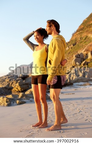 Full length portrait of smiling young couple standing at the beach - stock photo