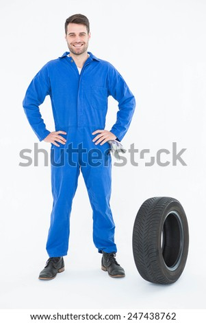 Full length portrait of smiling young male mechanic with hands on hips standing by tire on white background - stock photo