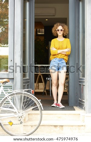 Full length portrait of smiling young tea house owner standing in shop entrance while waiting for her customers.