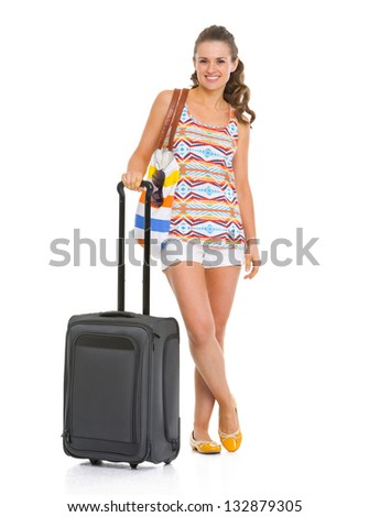 Full length portrait of smiling young woman with wheel bag going on vacation