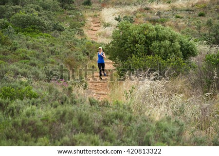 Full length portrait of sporty woman running on a dirt trail in nature - stock photo