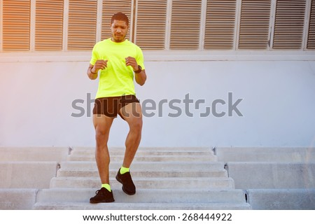 Full length portrait of sporty young man running down a flight of stairs while training outdoors at sunny afternoon,male runner dressed in bright t-shirt working out outdoors while doing legs exercise - stock photo