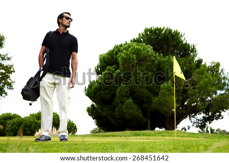 Full length portrait of stylish golfer man in glasses standing on beautiful golf course looking away, handsome brunette hair man with golf bag on shoulder and hand in pocket standing on golf course - stock photo