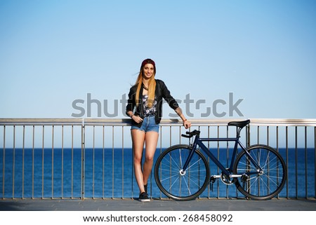 Full length portrait of stylish hipster girl standing with her sport fixed gear bike on the beach, young woman standing on the pier before ride along the seaside on her bicycle, promenade at sunny day - stock photo