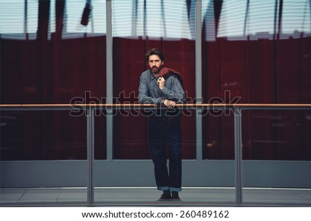 Full length portrait of stylish mature man standing interior beautiful big hall with glassy red color wall on background, male clothing designer, filtered image - stock photo