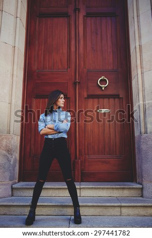 Full length portrait of stylish young hipster girl dressed in black trousers and denim shirt standing outdoors against large wooden door background with copy space for your text message or content  - stock photo