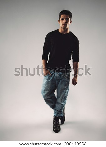 Full length portrait of stylish young man in casuals looking at camera. Hispanic male model posing on grey background. - stock photo