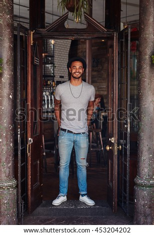 Full length portrait of stylish young man standing at the front door of a coffee shop. Trendy young man at a cafe entrance. - stock photo
