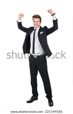 Full length portrait of successful businessman with arms raised standing over white background - stock photo