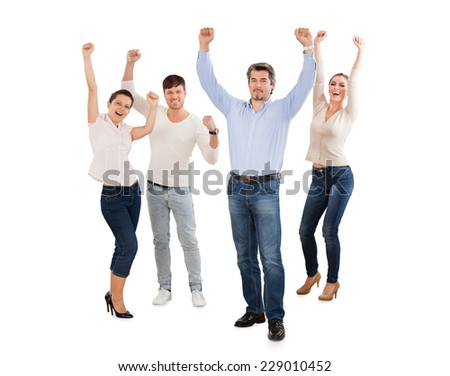 Full length portrait of successful businesspeople with arms raised standing against white background - stock photo