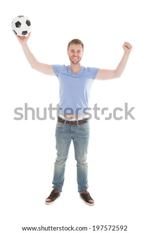 Full length portrait of successful man with arms raised holding soccer ball over white background - stock photo