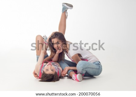 Full length portrait of teenage girls having fun, hugging and smiling with their legs up. Isolated on white background.  Concept of love, freedom, youth, friendship - stock photo