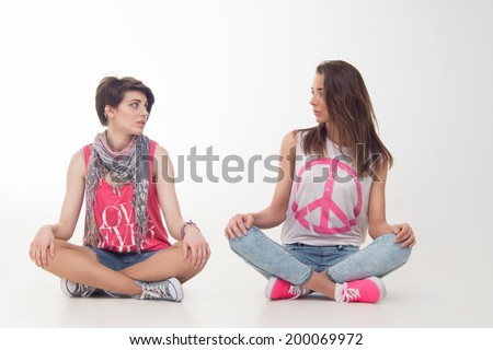 Full length portrait of teenage girls looking at each other sitting on the floor with their legs crossed. Isolated on white background. Concept of youth, friendship - stock photo