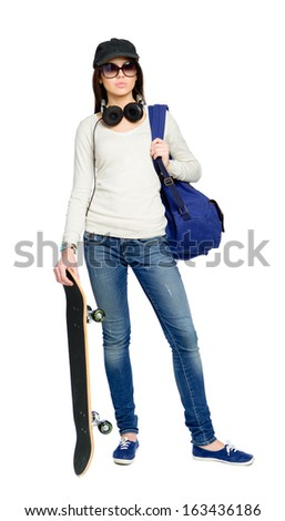 Full-length portrait of teenager with skateboard wearing sunglasses, peaked cap, earphones and rucksack, isolated on white. Concept of young generation - stock photo