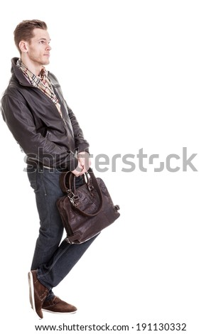 Full length portrait of thinking young man holding a leather bag and leaning against a wall  - isolated on white - stock photo