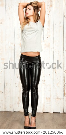 Full Length Portrait of Trendy Hipster Girl Standing at white Wall Background.Urban Fashion Concept.Copy Space,elegant leggings.street fashion patent leather punk print legging black,matte patent  - stock photo