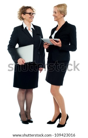 Full length portrait of two businesswomen discussing business isolated over white