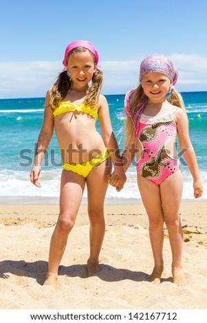 Full length Portrait of two girls in swimwear standing on beach. - stock photo