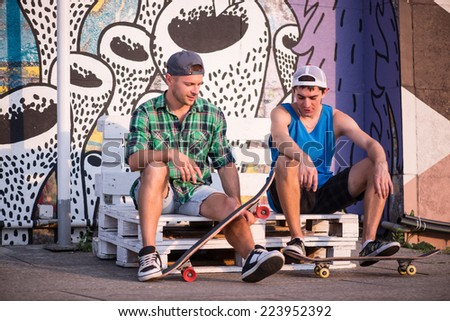 Full-length portrait of two young men sitting on the white bench on the street showing each other their skateboards talking about their favorite sport activity - stock photo
